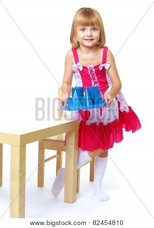 Little girl carrying a tray with cubes.