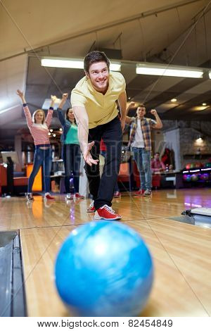 people, leisure, sport and entertainment concept - happy young man throwing ball in bowling club