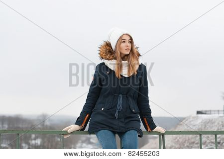 Cute Girl In Winter Cap And Jacket Sitting On The Railing. Outdoors In Winter.