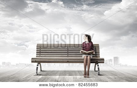 Young woman sitting on bench and reading book