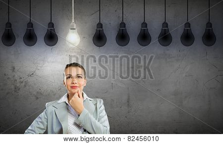 Portrait of pretty young businesswoman and many light bulbs around