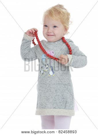 Smiling little girl put on her big red beads.