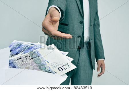 a man in suit taking an envelope full of pound sterling bills