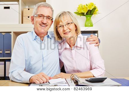 Happy senior couple with files and folders sitting at a desk