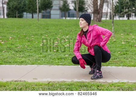 Young woman analyzing the track before running on a cold winter day in an urban park.