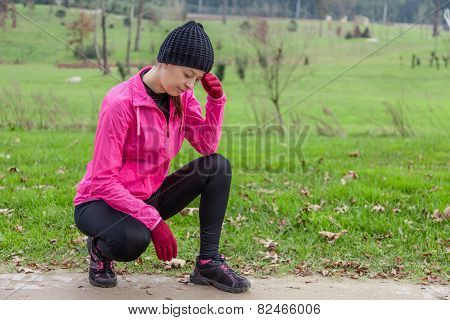 Young athlete woman feeling lightheaded or with headache on a cold winter day in the track of an urban park.