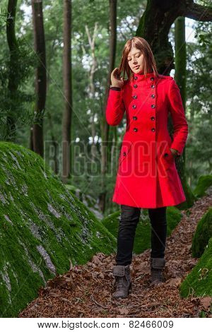 Young woman feeling sad walking on a forest wearing a red overcoat during winter under a sunlight ray