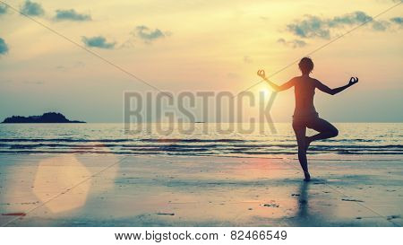 Silhouette of girl meditating on the sea beach. Yoga and fitness.