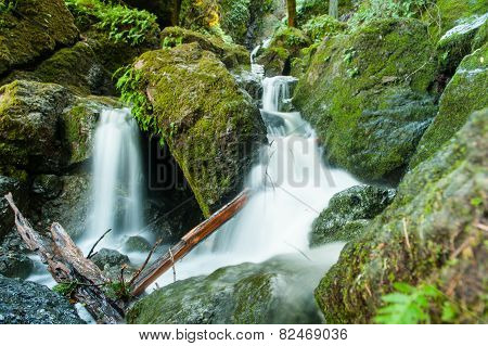 Waterfall Through A Moss Covered Rock Area
