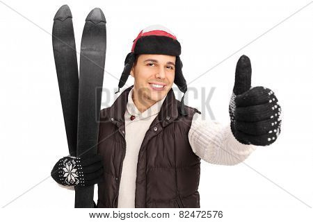 Young man posing with a pair of skis and giving a thumb up isoalted on white background