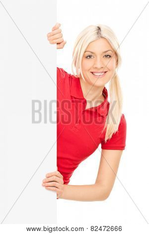 Young blond woman posing behind a blank panel isolated on white background
