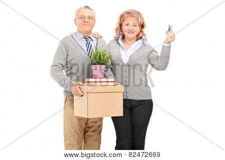 Mature couple holding moving boxes and keys isolated on white background