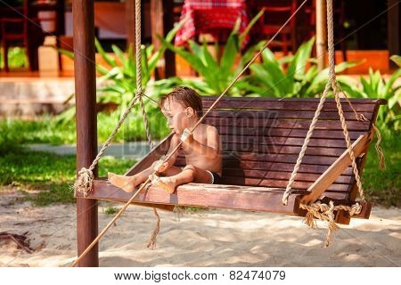boy on a swing at the beach