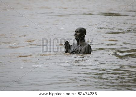 PRAGUE, CZECH REPUBLIC - JUNE 2, 2013: Statue of Indian spiritual leader Sri Chinmoy, partially flooded by the swollen Vltava River, on Kampa Island in Prague, Czech Republic.