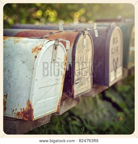 Rusty US mailboxes in the afternoon sun. . Filtered to look like an aged instant photo.