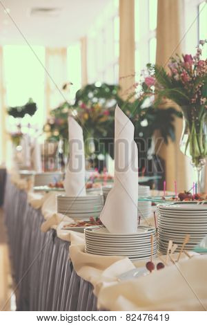 Table with dishware and tasty food waiting for guests, toned image