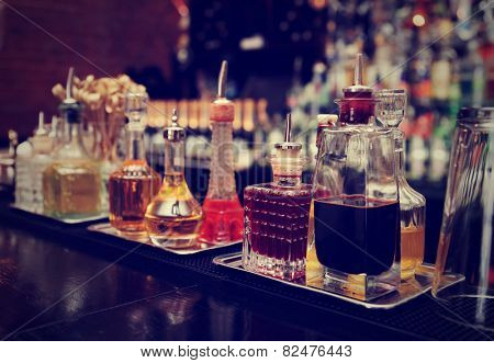 Bitters and infusions on bar counter, bar bottles in blurred background, toned image