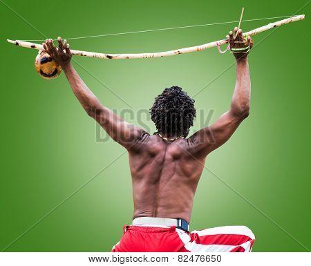 Brazilian performing Capoeira with Berimbau Instrument on green background
