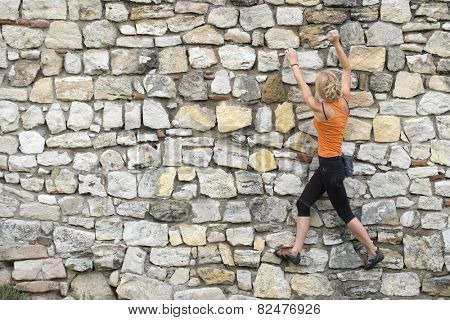 BELGRADE, SERBIA - JULY 29, 2014: young woman is training urban climbing on a wall of Kalemegdan Fortress in Belgrade. Shot in 2014
