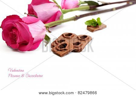 Chocolate hearts and red roses isolated on a white background