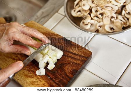Cutting the leek on wooden cutting board, slight movement blur might be noticeable