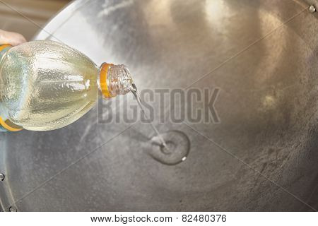 Pouring the oil inside the wok