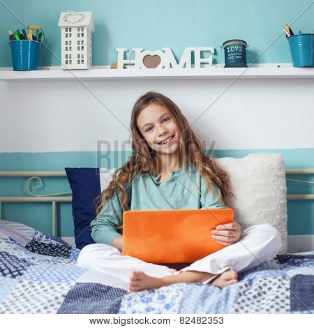 8 years old child having fun using laptop at her bedroom
