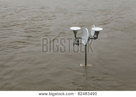 PRAGUE, CZECH REPUBLIC - JUNE 3, 2013: Street lamppost with a satellite dish partially flooded by the swollen Vltava River in Prague, Czech Republic.
