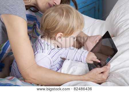 Baby Touching Tablet On Bed