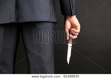 Businessman holding knife on gray background