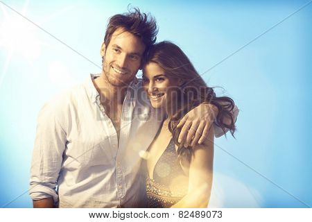 Happy romantic couple embracing at summer evening, smiling.
