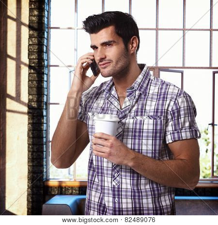 Handsome man talking on mobilephone, drinking coffee.