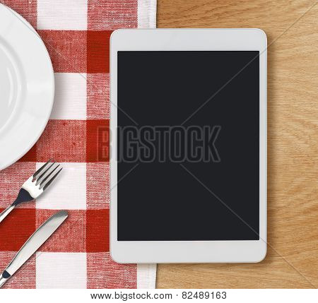 tablet pc looking lioke ipad on dinner table with fork and knife