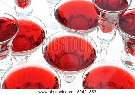 Alcoholic liquors in the crystal glasses isolated on white