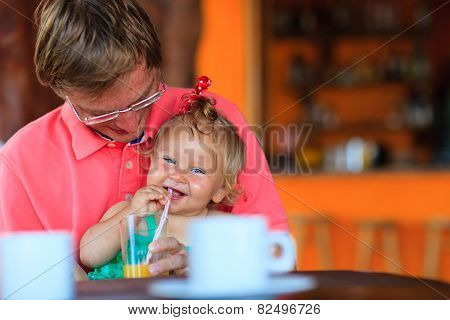 father and daughter having drink in cafe