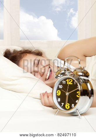 Sleeping woman resting in bed with alarm clock ready to wake her in the morning