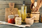 image of oil can  - Wooden kitchen utensils with glass bottle of olive oil and canned on wooden planks background - JPG