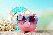 stock photo of piggy  - Piggy bank with sunglasses on the beach - JPG