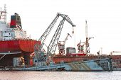 picture of dock  - Floating cargo crane and part of cargo ship at the shipyard docks - JPG