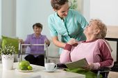 stock photo of nursing  - Helpful nurse working in old people - JPG