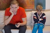 stock photo of boring  - Immature dad watching tv and his bored son - JPG