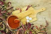 stock photo of cayenne pepper  - Wooden spoon of cayenne pepper in bowl with cayenne pepper on wooden table - JPG