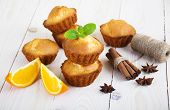 foto of bakeshop  - Homemade Muffins Ready for Breakfast with orange slices and cinnamon sticks on a wooden background