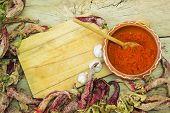 stock photo of pepper  - Wooden spoon of cayenne pepper in bowl with cayenne pepper on wooden table - JPG