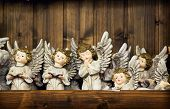 image of christmas angel  - Christmas angels toy with the sparked wings on a wooden wall background - JPG