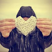 stock photo of telegram  - a young man under the rain showing a heart made - JPG