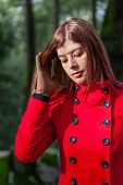 image of overcoats  - Young woman feeling sad walking on a forest wearing a red overcoat during winter under a sunlight ray - JPG