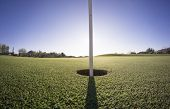 picture of angle  - Wide angle close up photo of golf course putting green and flag with sun low on horizon - JPG