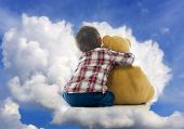stock photo of teddy  - Child sitting on heaven clouds with Teddy bear - JPG