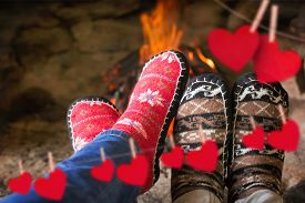 image of peg-leg  - Close up of romantic legs in socks in front of fireplace against hearts hanging on a line - JPG